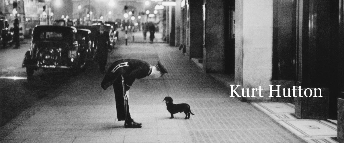 A hotel commissionaire talking to a small dachshund dog in Piccadilly Circus, London. Original Publication: Picture Post – 2 – In The Heart of the Empire – pub. 1938 (Photo by Kurt Hutton)