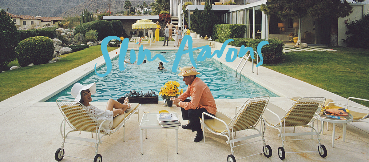 Desert Party by Slim Aarons. Lita Baron talking with a guest at a poolside party at Nelda Linsk's desert house in Palm Springs, California, January 1970. The house was designed by Richard Neutra for Edgar J. Kaufmann. (Photo by Slim Aarons) Open Edition or Limited Edition Estate Stamped Print (edition size 1/150).